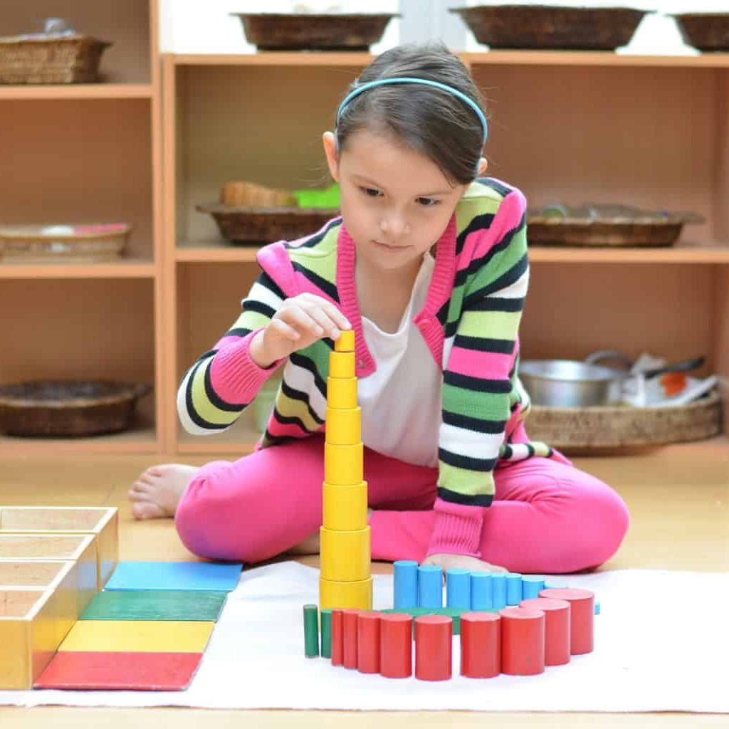 Little girl hand building tower made of montessori educational materials